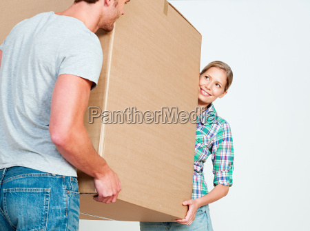 young couple carrying cardboard box