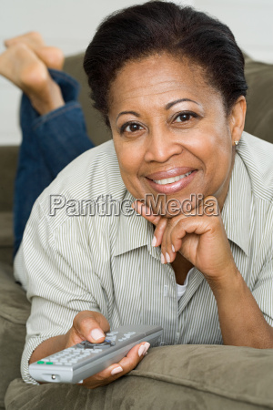 woman on sofa with remote control