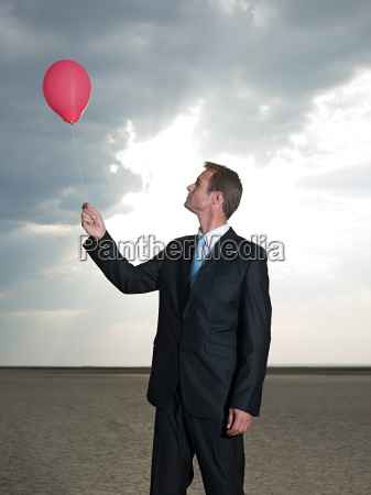 businessman holding a red balloon