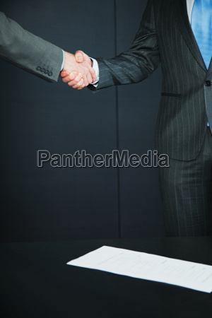 two businessmen shaking hands at job
