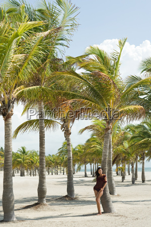 young woman on beach by palm