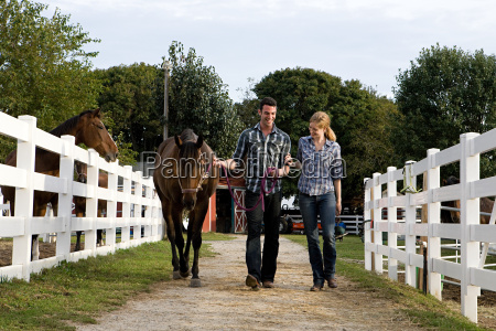two people with horse in paddock