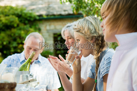 young woman drinking water with family