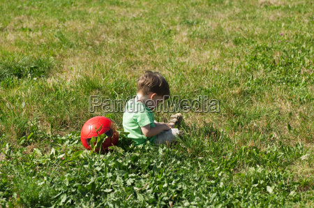 boy sitting in field with football