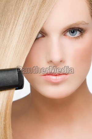 young woman using straightening irons