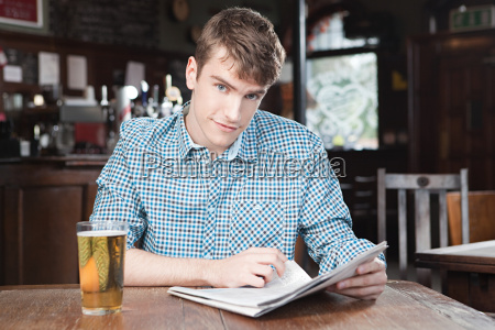 young man in bar with newspaper