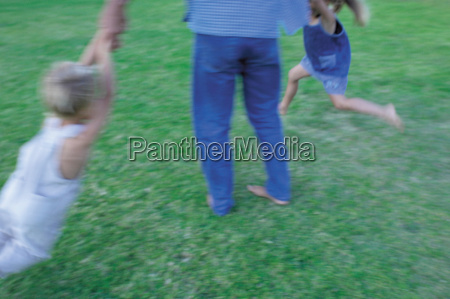 children swinging from fathers arms