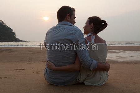couple sitting on beach at sunset