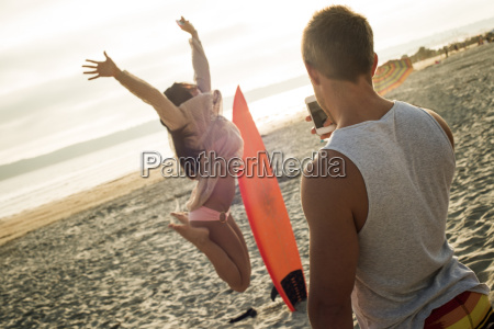 young man photographing woman jumping on