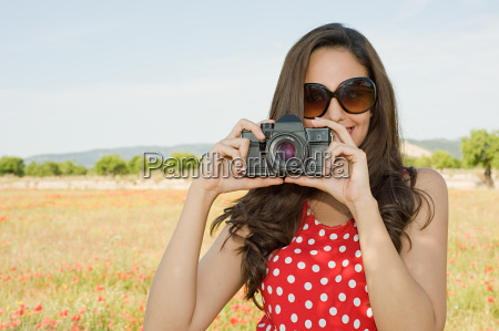 young woman with camera in poppy