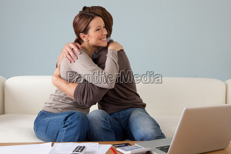 young couple embracing paperwork on table