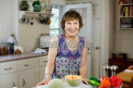 senior woman in kitchen with fruit