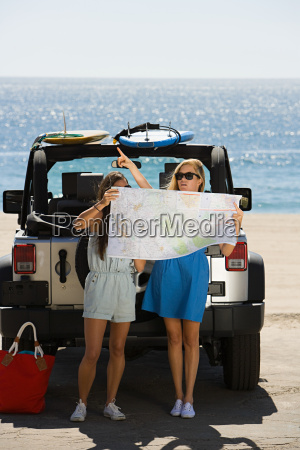 young women by vehicle looking at