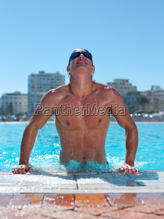 young man exiting swimming pool