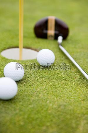 golf balls and golf hole close