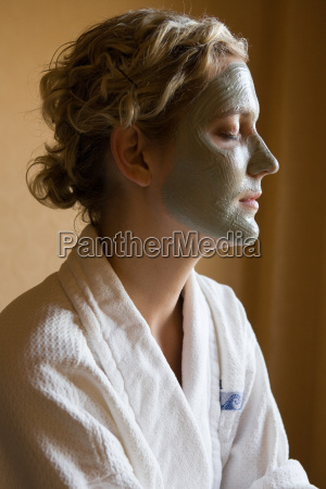 young woman with mud mask on