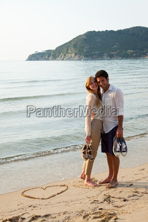 young couple on beach with heart