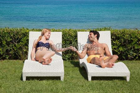 junges, paar, auf, liegestühlen, mit, händen - 18677776
