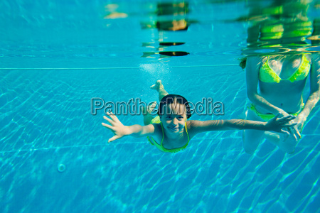 woman with girl swimming in swimming
