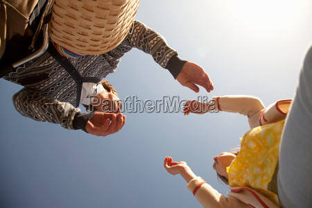 low angle view of couple reaching