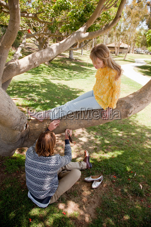 young man carving tree that woman