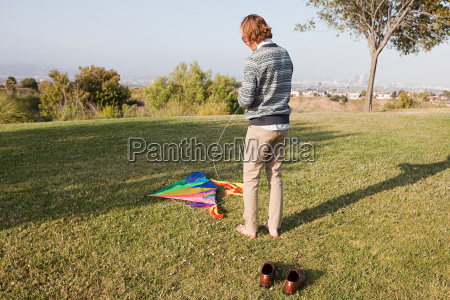 young man in field with kite