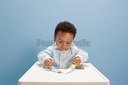baby boy sitting in highchair using