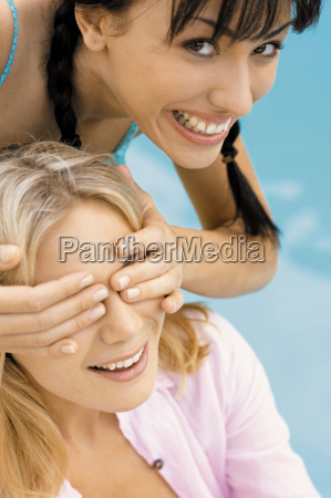 woman covering anothers eyes