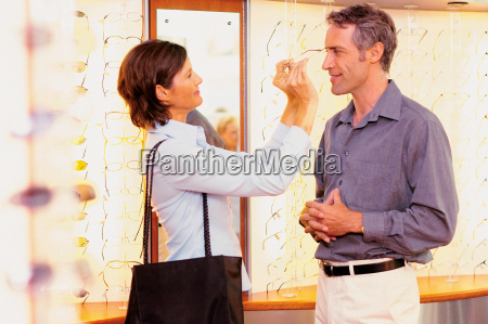 man and woman choosing spectacles