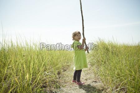 portrait of female toddler holding long