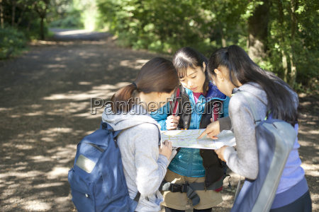 three young female hikers looking at