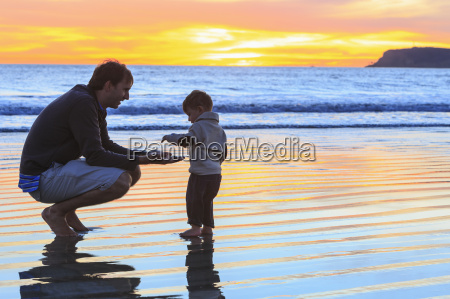 father and toddler son playing on