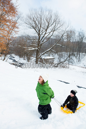 two children sledging in snow
