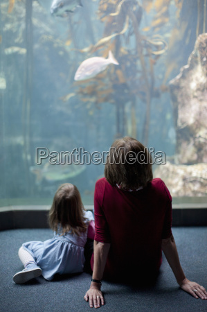 young girl and grandmother watching fish