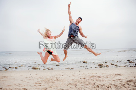 pregnant couple jumping mid air on