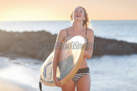 young woman carrying surfboard on beach