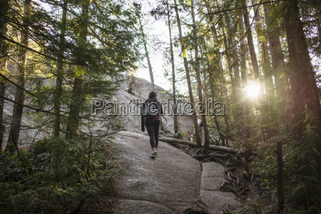 young woman walking through forest squamish