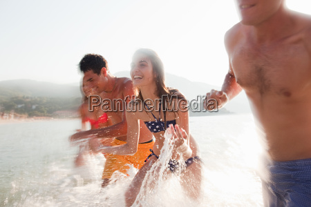 young friends splashing in the sea