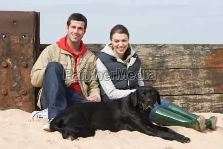 couple sitting with pet dog at