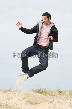 young man jumping on a beach