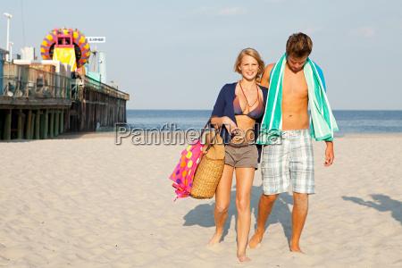 teenage couple walking on beach