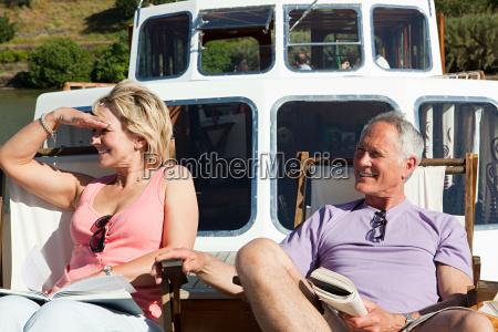 senior couple sitting on deckchairs on