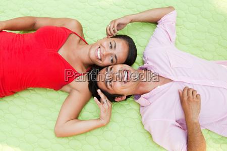 mid adult couple lying on blanket