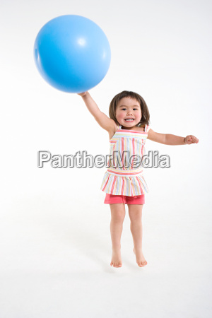 a girl jumping with a ball