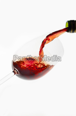 bottle of red wine being poured