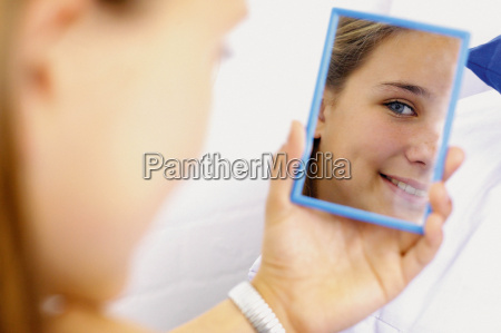 teenage girl looking in mirror