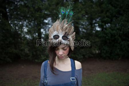 junge frau mit gefiederter maske auf