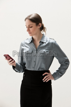 young businesswoman using cellphone studio shot