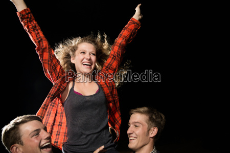 two male friends lifting teenage girl
