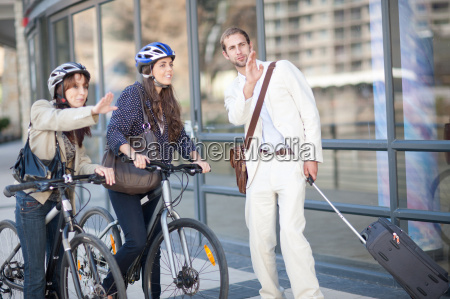 young women with bicycles asking young